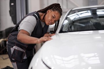 Fototapeta Confident Afro american Female auto mechanic touching surface of white repainted and clean car body in auto repair shop. Pretty black woman Mechanic in uniform working in workshop, looking serious obraz