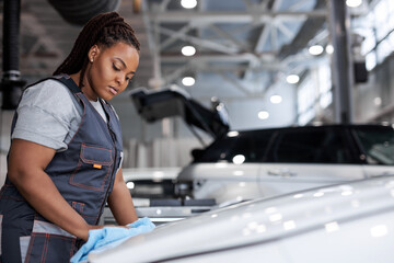 Fototapeta african american Female Worker in gray uniform cleaning car. auto detailing and valeting, service concepts. serious lady at work in car service, side view obraz