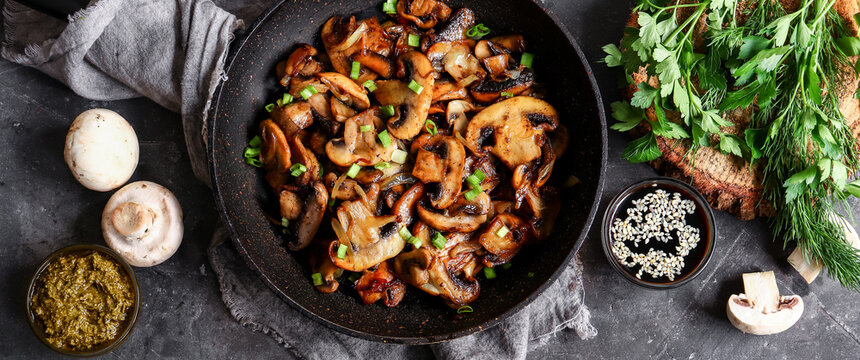 Roasted mushrooms with onion in frying pan on a dark background. Top view. Food banner