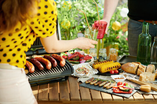 table with electric grill and grilled sausages