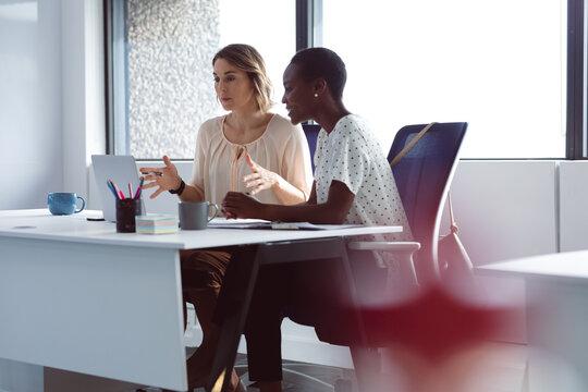 Two diverse businesswomen sitting at desk, looking at laptop, talking