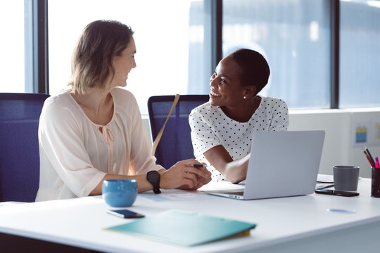 Two diverse businesswomen sitting at desk, talking and smiling