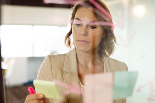 Caucasian businesswoman making notes and adding post-ins on transparent board