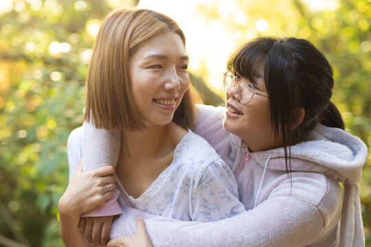 Portrait of smiling asian woman with her daughter embracing in garden
