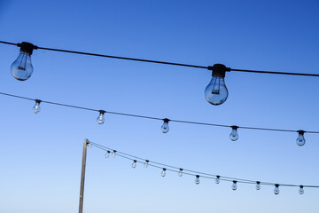 Hanging garland light bulbs with blue sky background or backdrop.
