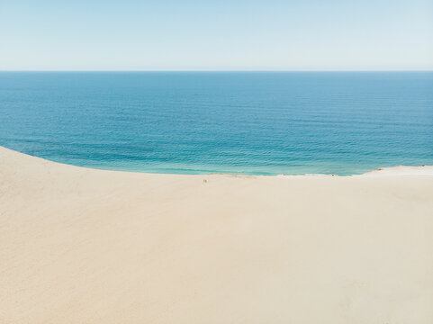 Aerial view of two people standing on Carlo Sandblow and looking down on the ocean, Queensland, Australia.
