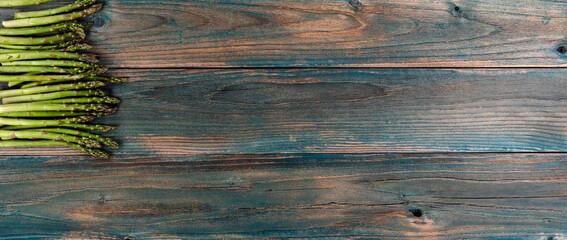 Obraz Fresh organic asparagus on faded blue wood planks in overhead view - fototapety do salonu
