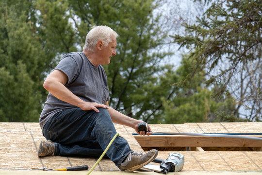 Older man working on measuring for roof