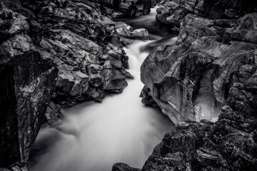 Long exposure of flowing water in Verzasca River at Lavertezzo - clear and turquoise water stream and rocks in Ticino - Valle Verzasca - Valley in Tessin - Travel destination in Switzerland Wall mural
