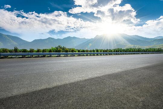 Asphalt highway and mountain landscape at sunset,road pavement background.