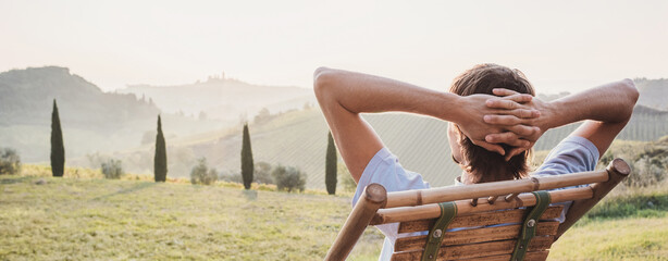 Obraz Young man looking at the valley in Tuscany, Italy, relaxation, vacations, lifestyle, summer fun, have a good day, enjoying life concept. Panoramic banner. - fototapety do salonu