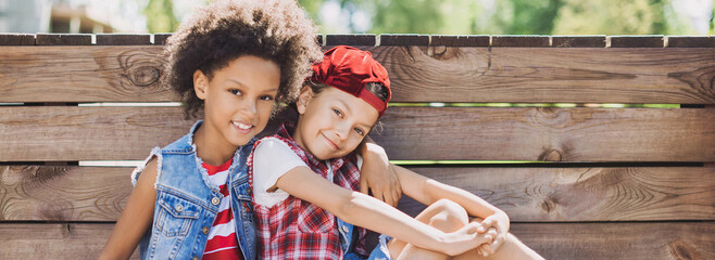 Fototapeta Two little girls outdoor portrait. Diverse multi ethnic kids friends playing together. Summer fun, friendship, diversity, vacations concept obraz