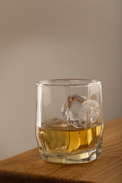 Whiskey or alcoholic beverage, with ie in a square formed designer glass. Sitting on an Oak table, with a backlighted gray surface.