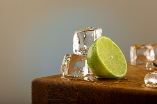 A lime or lemon with blocks of ice melting on an oak table, with a blue shined background on a grey surface. With dipping water from the table.
