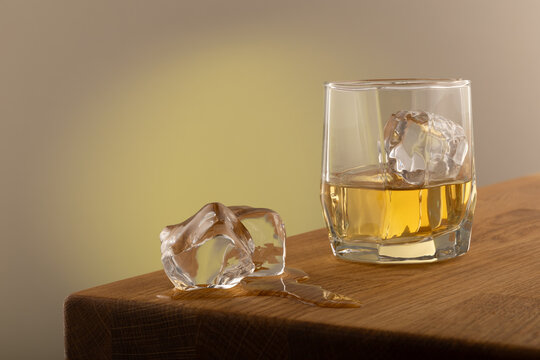 Whiskey or alcoholic beverage, with ie in a square formed designer glass. Sitting on an Oak table, with a backlighted gray surface. With melting Ice cubes on the side of the glass.