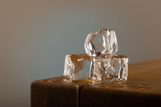 3 blocks of ice melting on a oak table, with a blue shined background on a grey surface. With dipping water from the table.