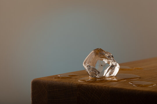 1 block of ice melting on a oak table, with a blue shined background on a grey surface. With water on the oak table.