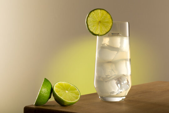 Lemon lime drink in long glass with lime fruits on the left of the shot. In the glass there is ice with light coming trough. Is shot on a grey background with a green yellow glow.