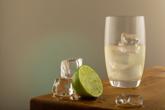 Lemon lime drink in long glass with lime fruits and ice on the left of the shot. In the glass there is ice with light coming trough. Is shot on a grey background with a green yellow glow.