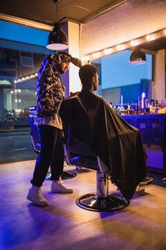 Black man having haircut with electric clipper machine