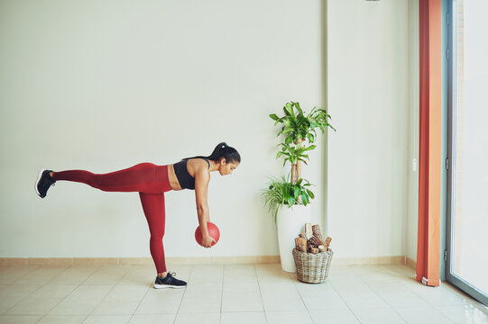 Ethnic athlete leaning forward with fitness ball in room