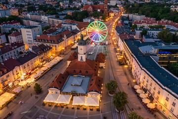 Obraz Białystok, widok z lotu ptaka o zmierzchu na Ratusz, Rynek Kościuszki i koło widokowe - fototapety do salonu