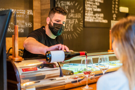 Barman in mask pouring red wine in cafe