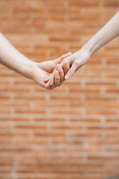 Crop romantic couple holding hands