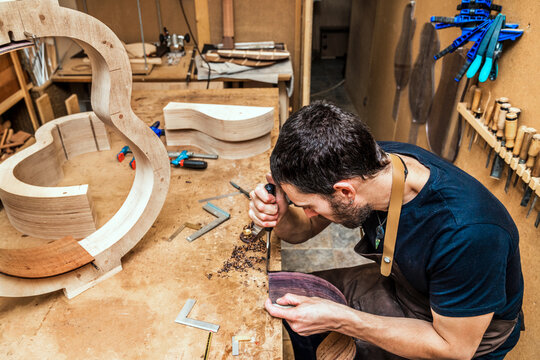 Luthier with rasp building guitar at table in workroom
