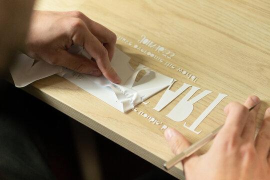 Crop unrecognizable person transferring cutout letters on transparent tape