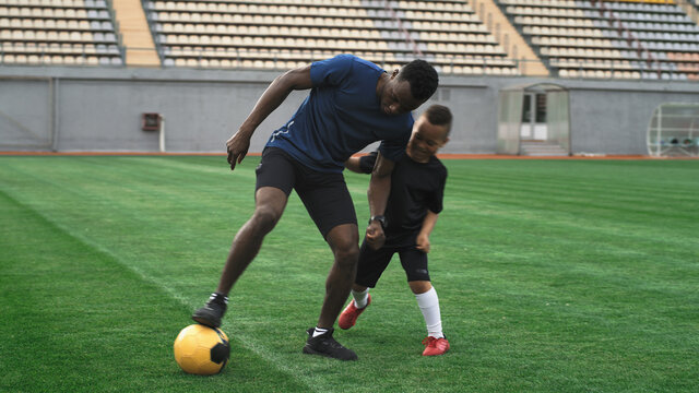 Diverse father and son playing football on stadium