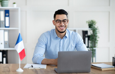 Online foreign languages tutoring. Cheerful Arab male teacher giving French class, communicating on...