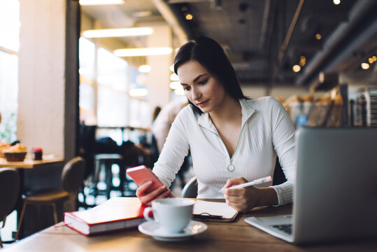 Serious woman using smartphone during remote work