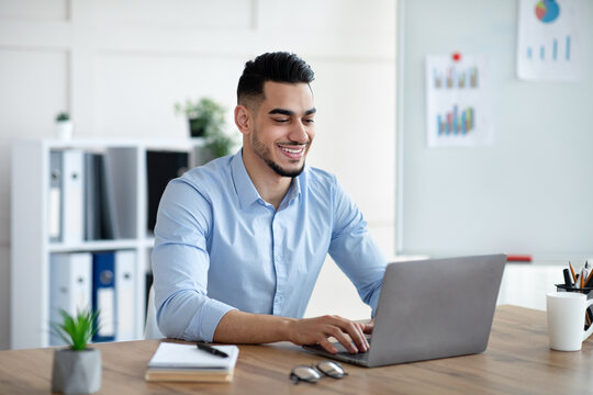 Handsome young Arab businessman working with laptop computer at his desk in office