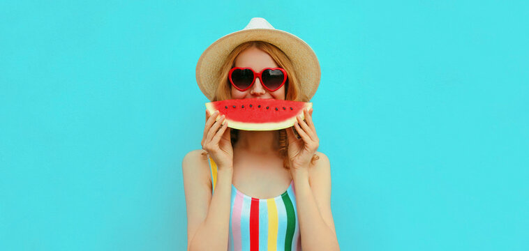 Summer portrait of happy smiling young woman with slice of watermelon wearing a hat on blue background