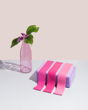 Various pink fitness elastic bands and purple yoga block on pastel beige background. Glass bottle and beautiful magnolia flower. Spring or summer home or gym workout scene.