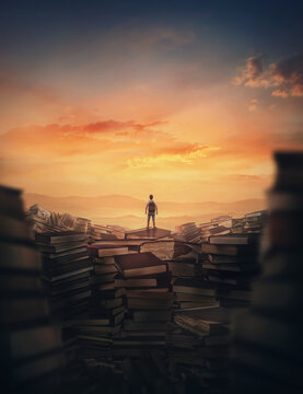 Surrealistic scene with a tiny man climbing on the top of a huge books landfill. Different thrown book piles and a person silhouette against sunset. Educational concept, in search of knowledge