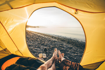Fototapeta Sunrise With Coffee. View through tent man and woman making coffee at sea beach. Summer camping vacation. obraz
