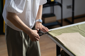Fototapeta Tailor cut fabric patterns to sew garment. Freelancer dressmaker or self employed fashion designer work in atelier. Closeup shot of female sewer hand holding scissors and material on table in workshop obraz