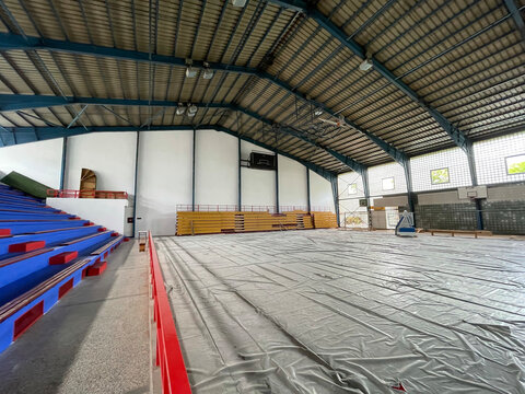 Construction site of sports hall, basketball court renovation, school gym indoor changing hardwood parquet flor and insulation.
