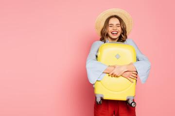 Fototapeta Positive woman in sun hat hugging suitcase on pink background obraz