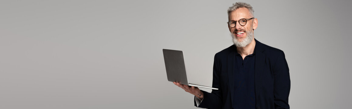 cheerful middle aged man in glasses holding laptop isolated on grey, banner