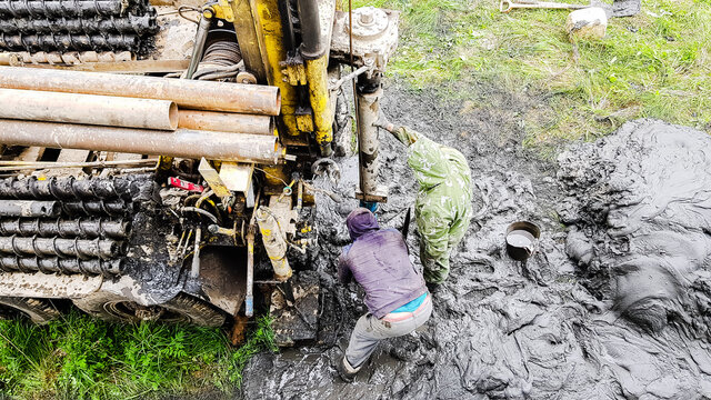 two men in dirty clothes are drilling a well with a drilling rig. special machine with screw drill.