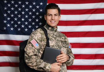 Obraz Cadet with backpack and tablet against American flag. Military education - fototapety do salonu
