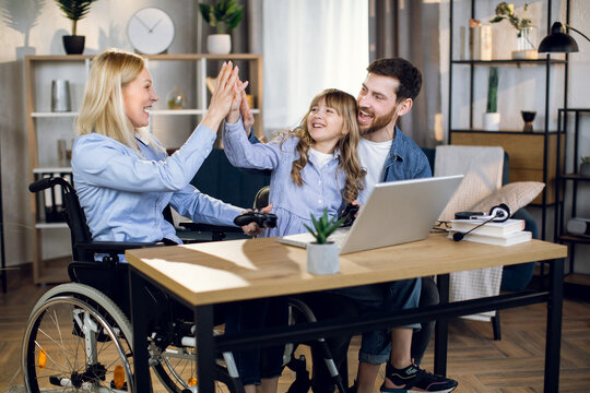 Young woman in wheelchair giving high five to cute daughter and handsome husband. Happy family playing video games on laptop at home. Positive feelings and emotions.