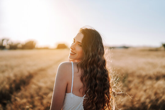 Chica joven atractiva posando en mitad de un campo de trigo al atardecer con tonos dorados