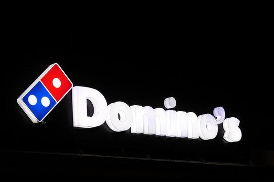 Domino's Pizza store sign illuminated over night sky