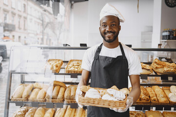 Fototapeta African American baker holding tray of bread in bakery obraz