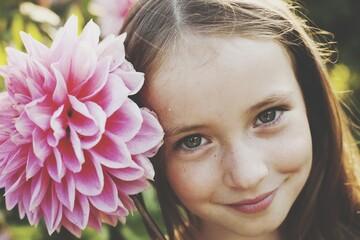 Fototapeta Close-up Portrait Of Smiling Girl With Pink Flower obraz
