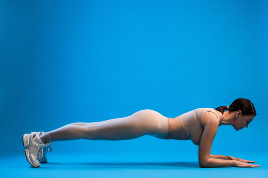 Woman standing in forearms plank pose on blue background